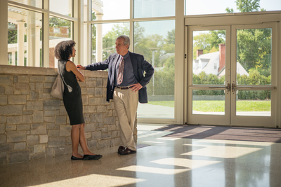 A man and woman standing in a well-lit lobby make casual conversation in front of a stone brick wall